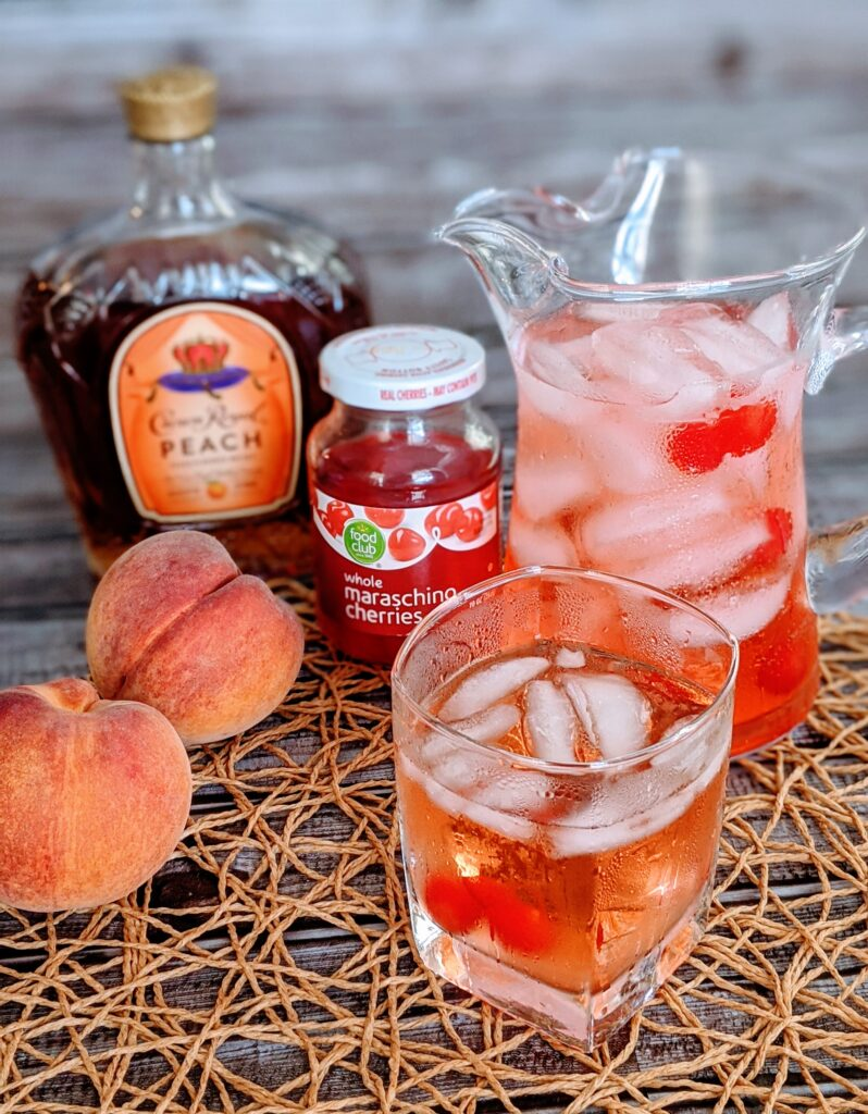 Crown Royal Peach accompanied by peaches, and cherries.  Shaken drink in a highball glass and pitcher.