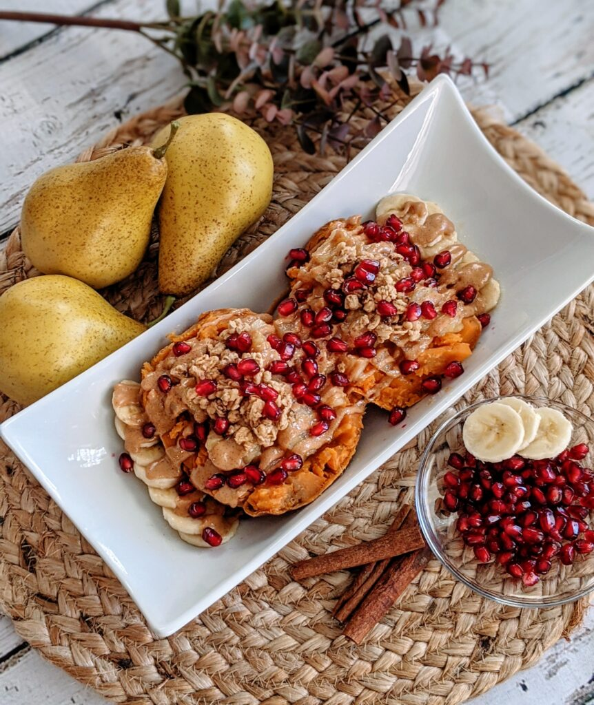 Plated super sweet potato medley surrounded by pears, cinnamon sticks, sliced banana and pomegranate.