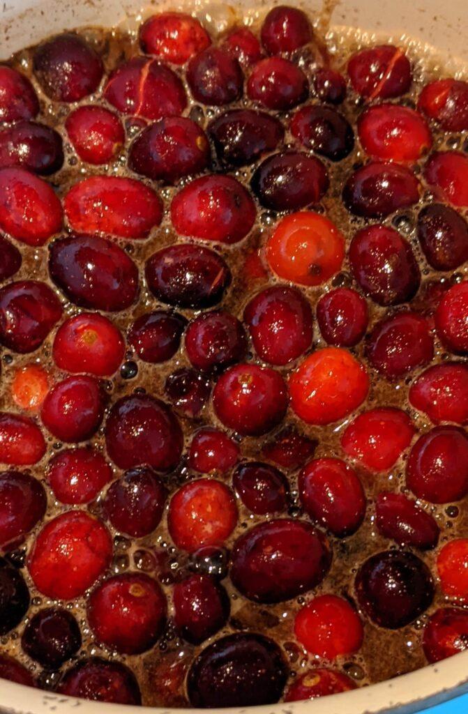 Boiling cranberries in saucepan adding brown sugar, vanilla and cinnamon... almost ready.