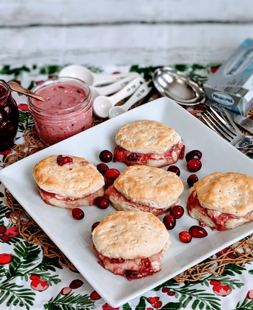 Cranberries & Cream Biscuits on white square plate, surrounded with measuring spoons, cranberry and cream sauce in a jar.