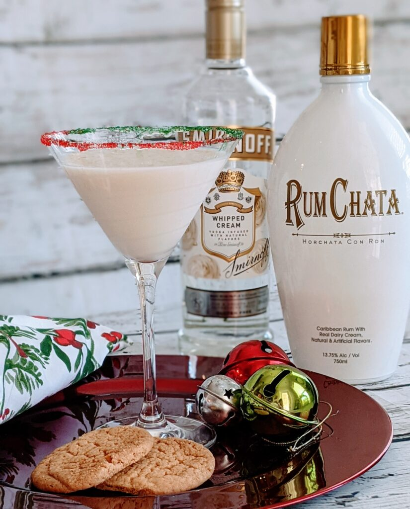 Sugar Cookie Martini on a decorative plate surrounded by Smirnoff Whipped Cream and Rum Chata.