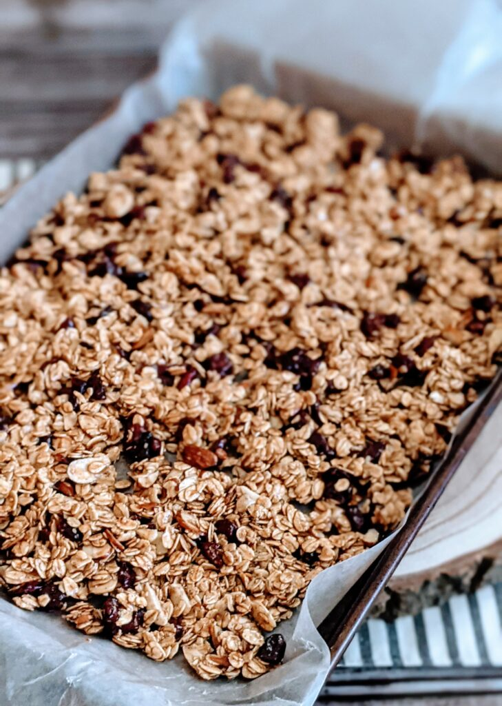 Granola spread on parchment covered baking sheet.