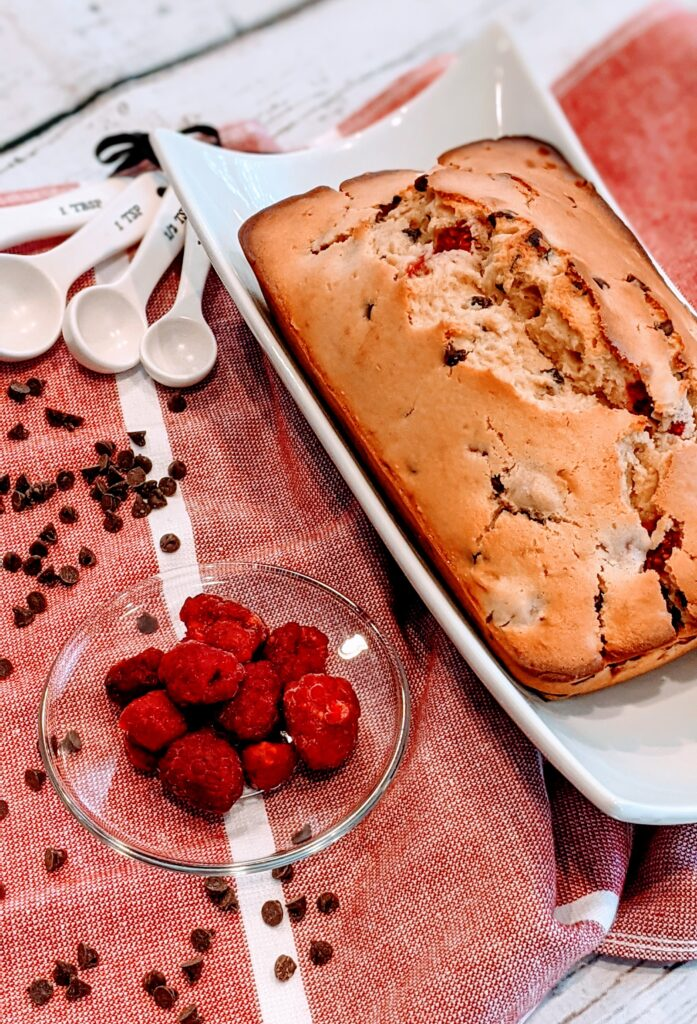 Raspberry Chip Muffin Bread fresh from the oven with sides of raspberries and chocolate chips.