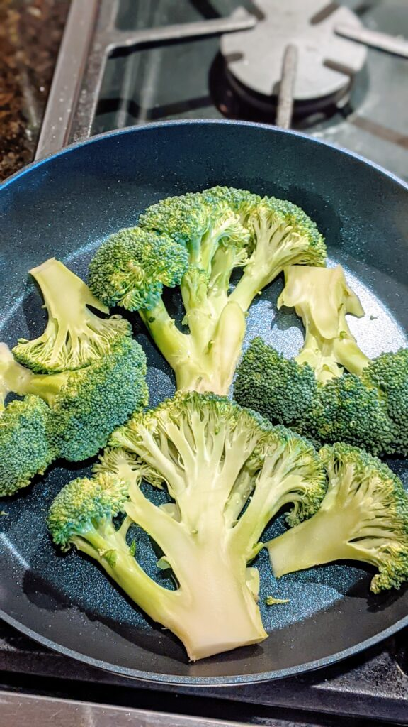 Broccoli steaks ready to be steamed in a skillet.