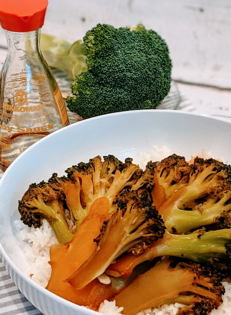 STEAMED TERIYAKI  BROCCOLI STEAKS on a white serving dish with white rice and surrounded with ingredients.