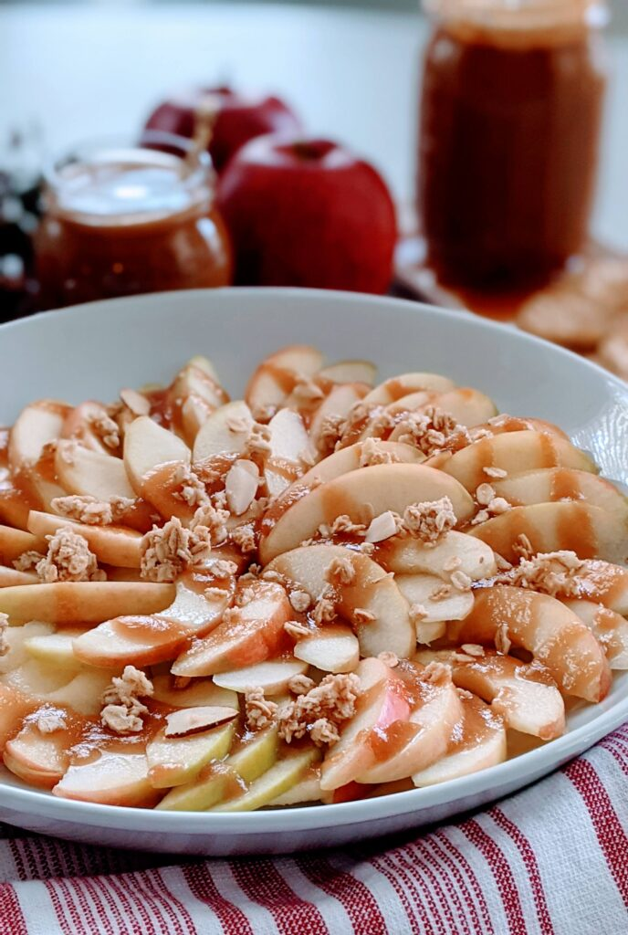 Salted caramel drizzled over apples with granola on top.