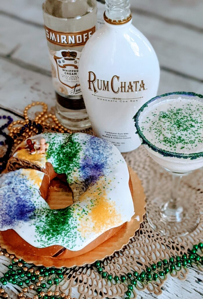 King Cake Frozen Martini alongside Rum Chata, Smirnoff vodka, and a King cake.  All surrounded with decorative purple, gold and green beads.