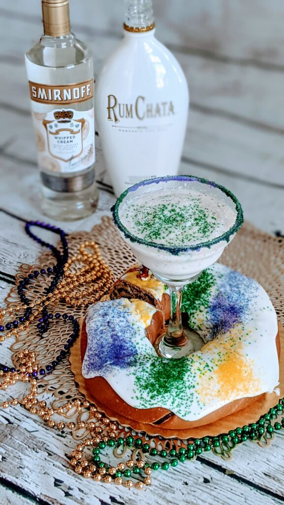 Martini set inside middle of king cake.  Rum Chata, Smirnoff vodka, and a King cake surrounding.  Decorative purple, gold and green beads.