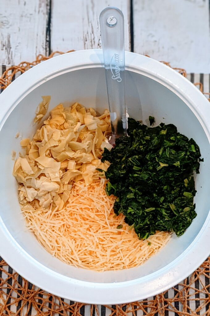 Artichoke, spinach, and parmesan cheese and  cream cheese in a mixing bowl.
