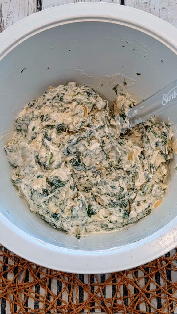 Artichoke, spinach, and parmesan cheese and  cream cheese stirred in a mixing bowl.