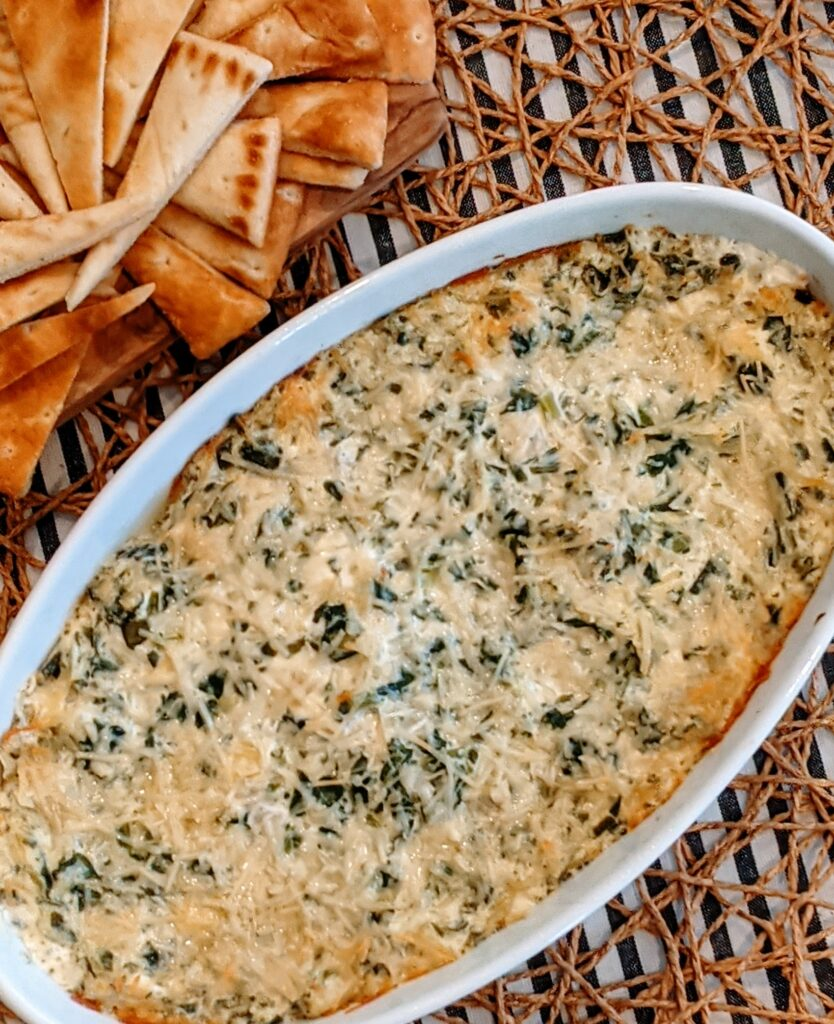 Easy Creamy Spinach Artichoke in oval serving bowl, with a side of Greek pits bread.