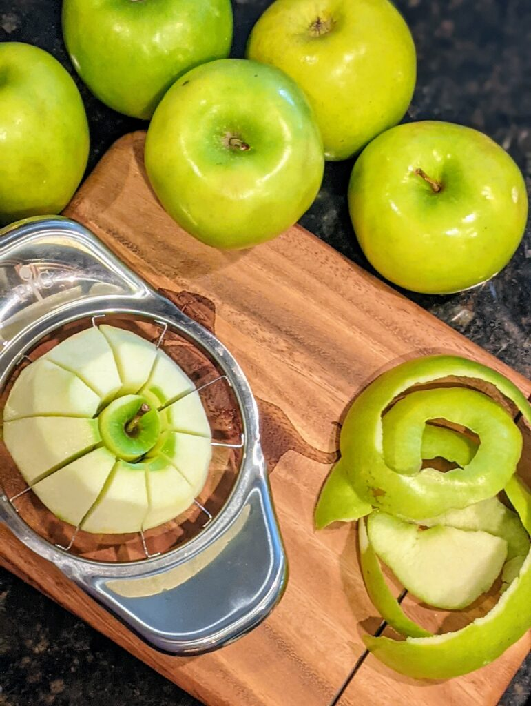 Peeling and slicing apples on a wooden cutting board.