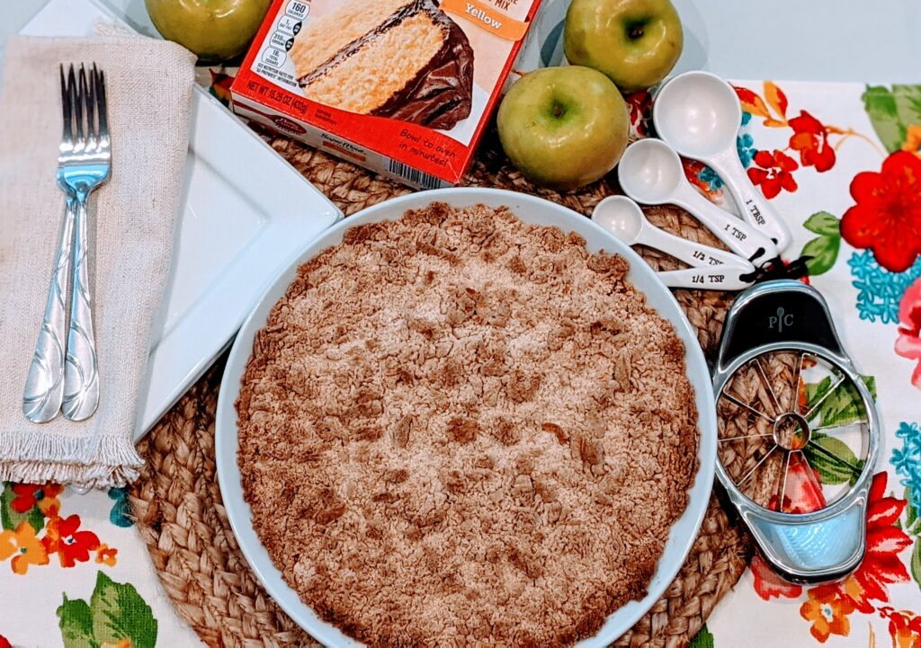 5 Ingredient Apple Crisp fresh from the oven on place setting with surrounding ingredients.