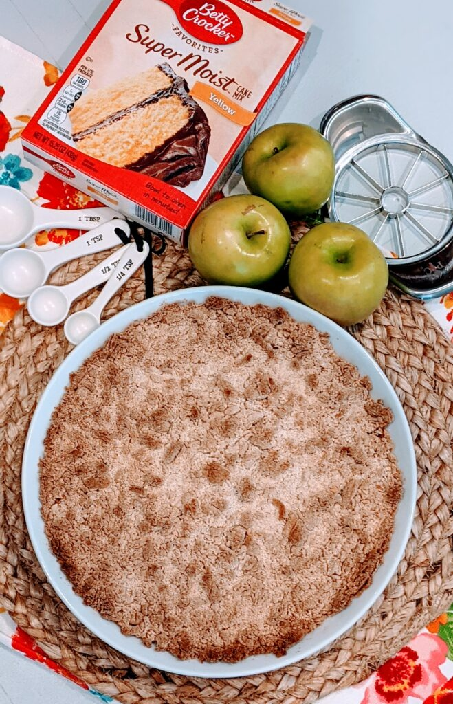 5 Ingredient Apple Crisp fresh from the oven on place setting with surrounding ingredients and utensils.