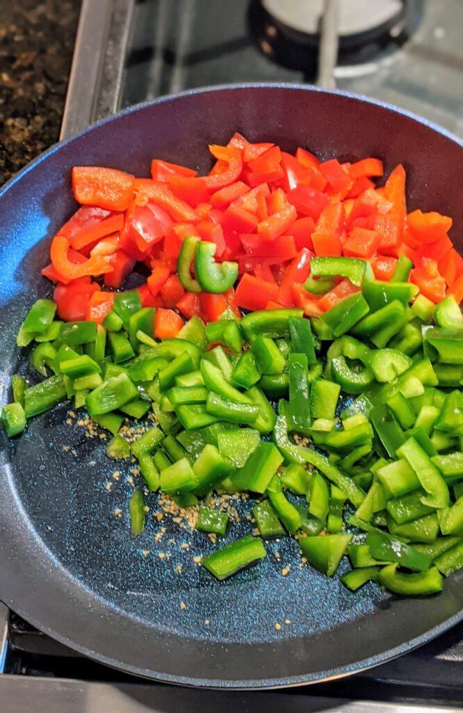 Peppers sautéing in skillet.