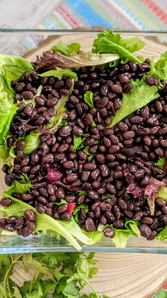 Spring salad in a clear square serving bowl topped with black beans.
