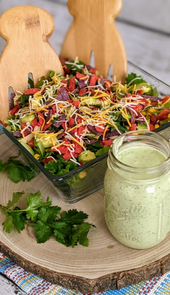 Loaded Southwest Salad with Avocado Cilantro Dressing in a clear square serving bowl.