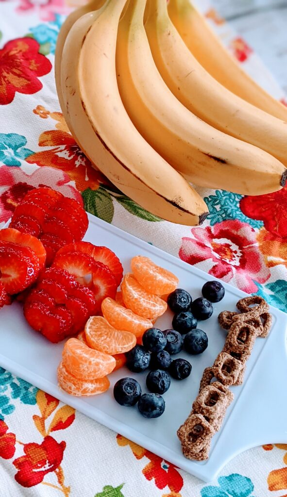 Fruit on white cutting board prepared to place in Fun Fruity Breakfast Bowl.