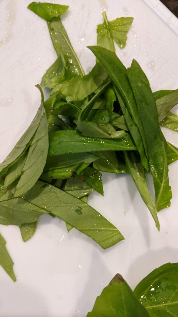 Sliced fresh basil on cutting board.