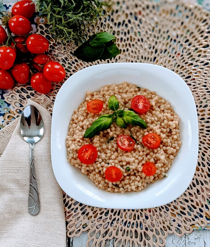 Completed Vegan Basil Garlic Couscous in a white plated bowl aside a spoon and cherry tomatoes and spices.