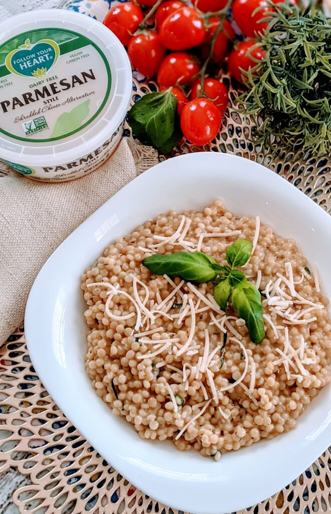 Completed Vegan Basil Garlic Couscous in a white plated bowl topped with vegan parmesan cheese and fresh basil.