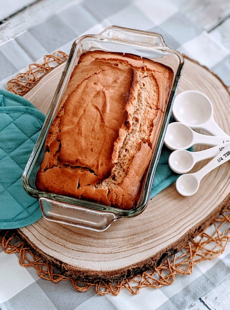 Vegan Peanut Butter Bread fresh form the oven on serving platter along with hot pads and measuring spoons.