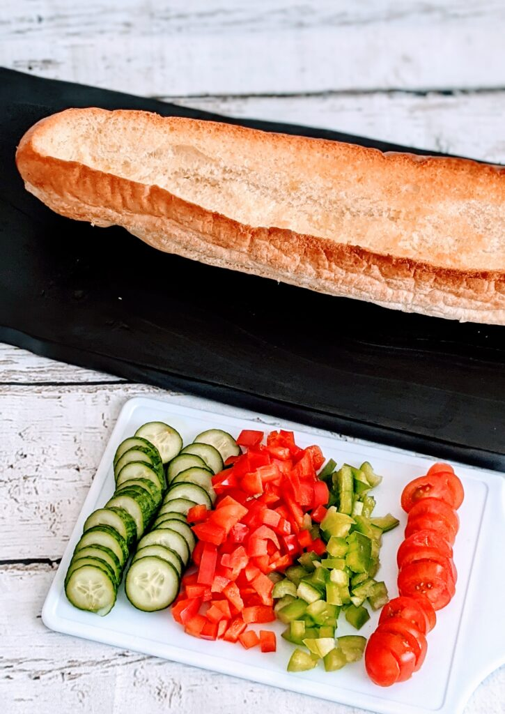 Baked sub aside diced peppers, sliced cucumber and tomato toppings.