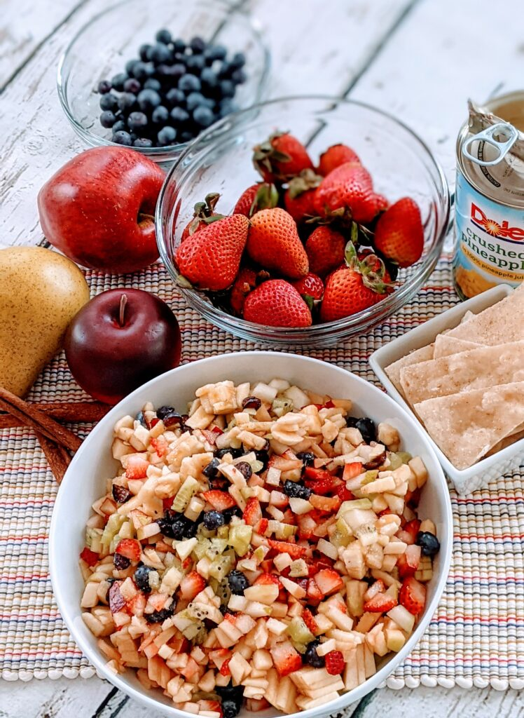 Finished Cinnamon Sugar Fruit Salsa in large white serving bowl, surrounded with ingredients.  Cinnamon, sugar tortilla crisps on the side.