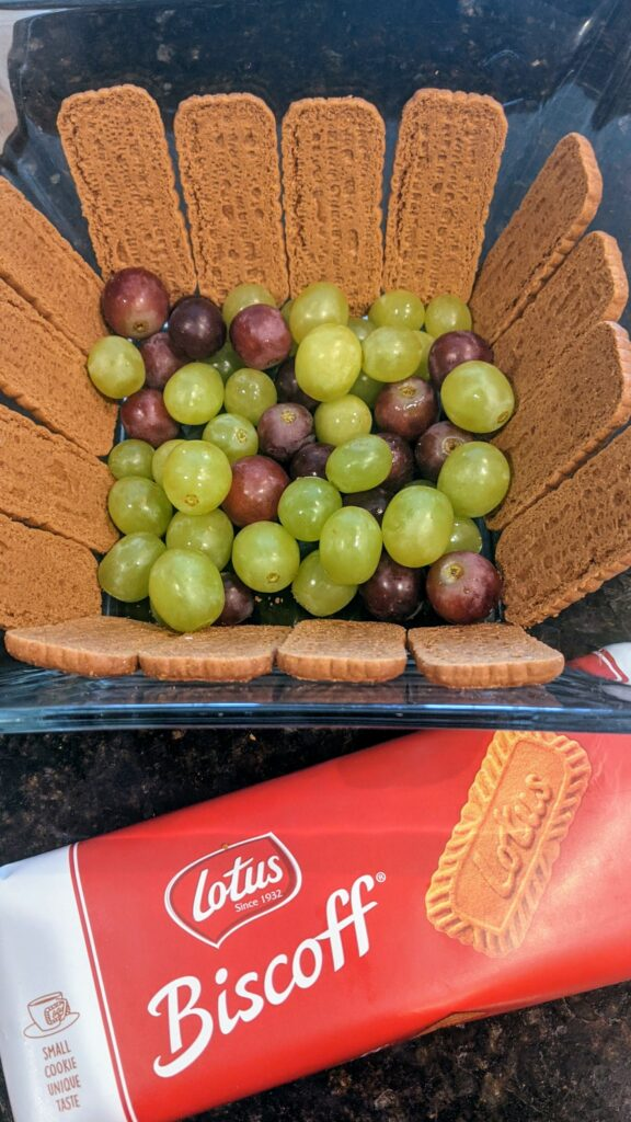 Layered Biscoff cookies along sides of bowl and grapes on the bottom of bowl.