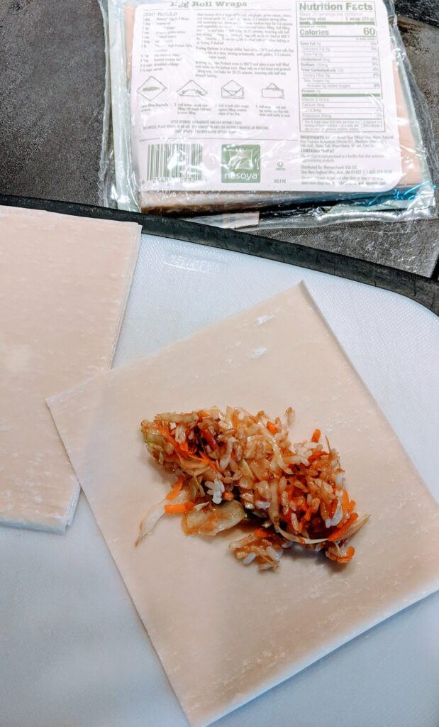 Taking 1 egg roll wrap place about 2-3 Tbsp. of coleslaw/rice mixture in diagonally in center of egg roll wrap.