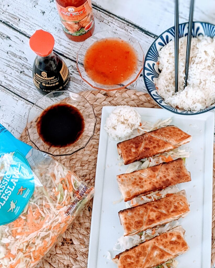 VEGAN SLAW EGG ROLLS on white, rectangular serving plate.  Sides of mae ploy, soy sauce, coleslaw and bowl of extra white rice.