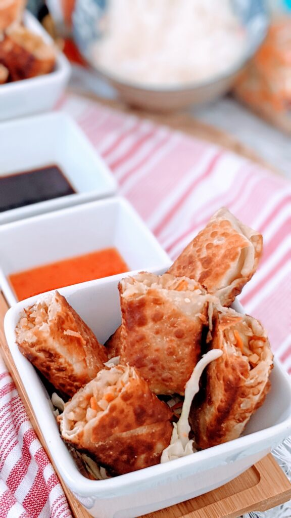 Close up of egg rolls in a small white bowl alongside soy sauce and mae ploy.