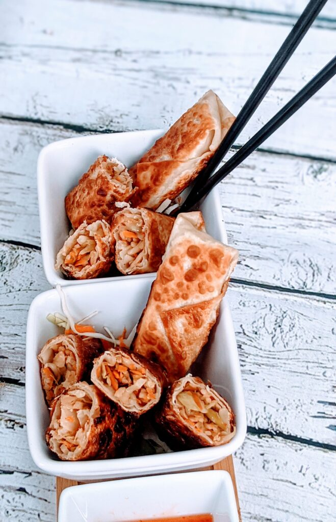 Over top view of egg rolls in small, squared,white bowls.