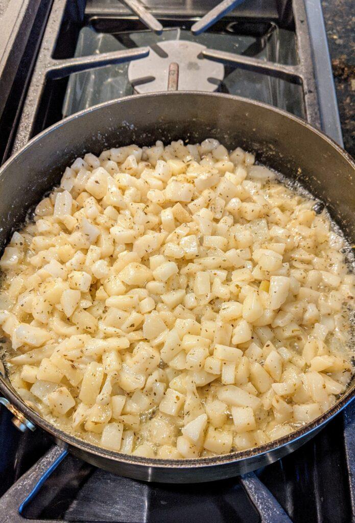 Home fries in skillet with seasonings.