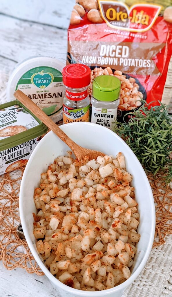 Finished GARLIC PARM HOME-FRY BAKE in white serving dish, surrounded with ingredietns.