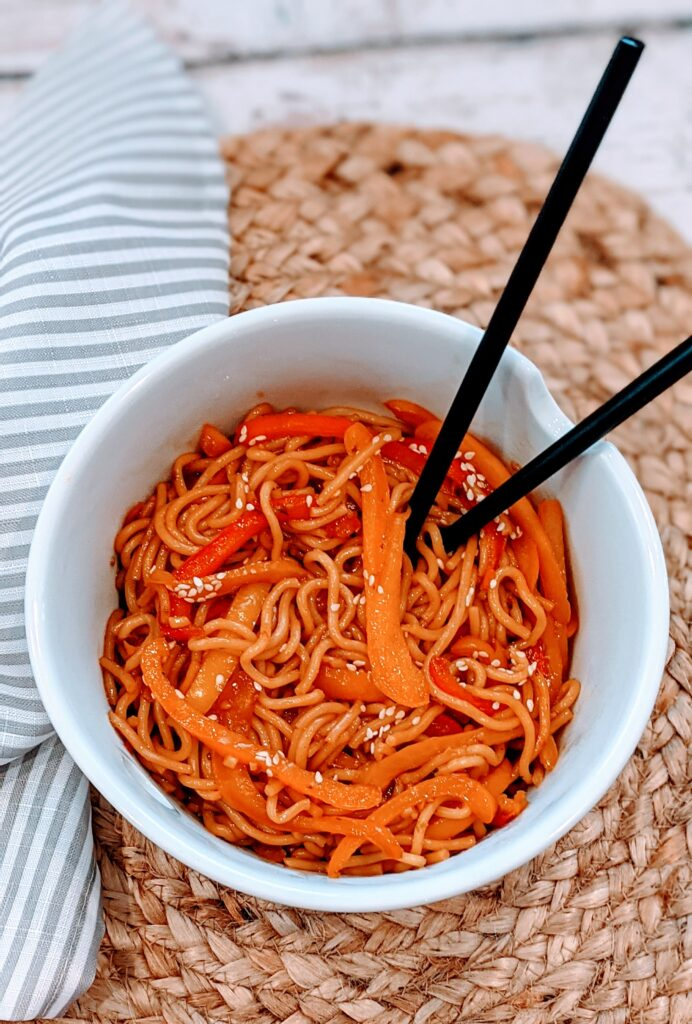 Easiest Stir Fry Noodles in white serving bowl with chopsticks.