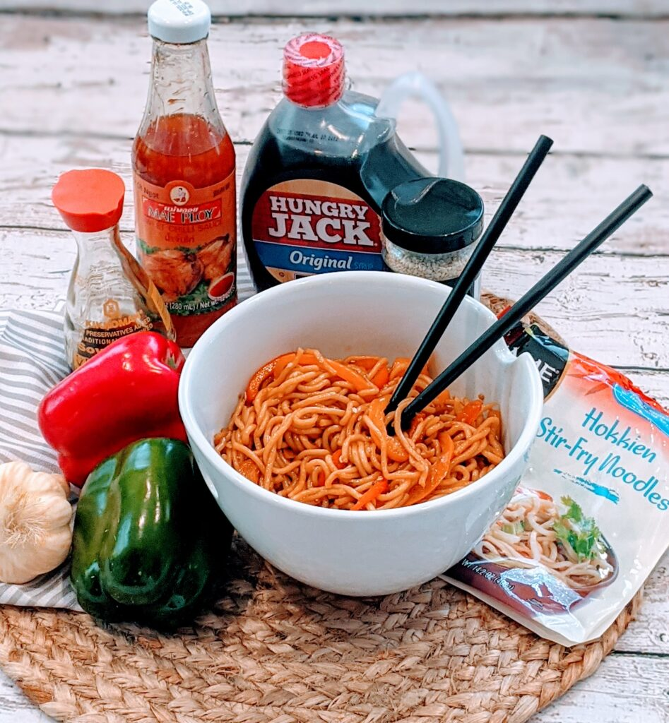 Easiest Stir Fry Noodles in a white serving bowl, with chopsticks.  Ingredients surrounding.