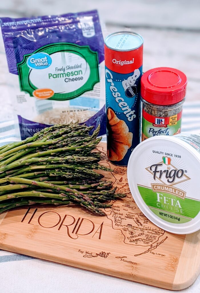 Ingredients for CRESCENT ROLLED FETA ASPARAGUS on wooden cutting board with the state of Florida.