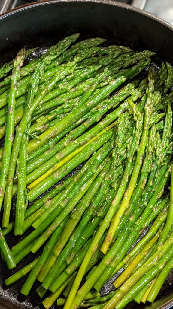 Sautéed asparagus in skillet ready to be wrapped in crescent roll.