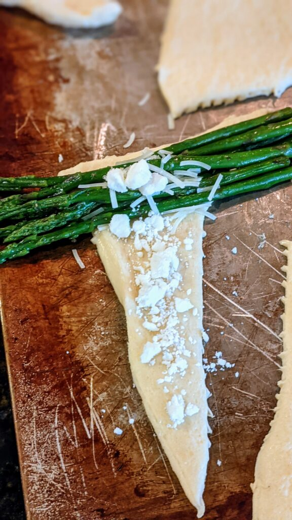Cheese added to asparagus and triangle crescent roll.