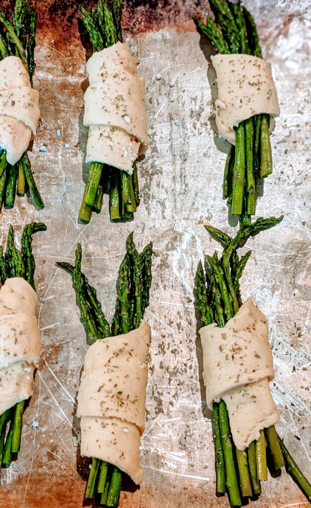 Wrapped and seasoned asparagus on baking sheet.