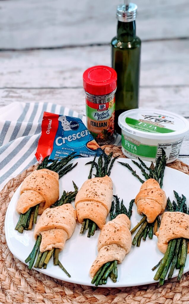 CRESCENT ROLLED FETA ASPARAGUS on white serving plate with surrounding ingredients.