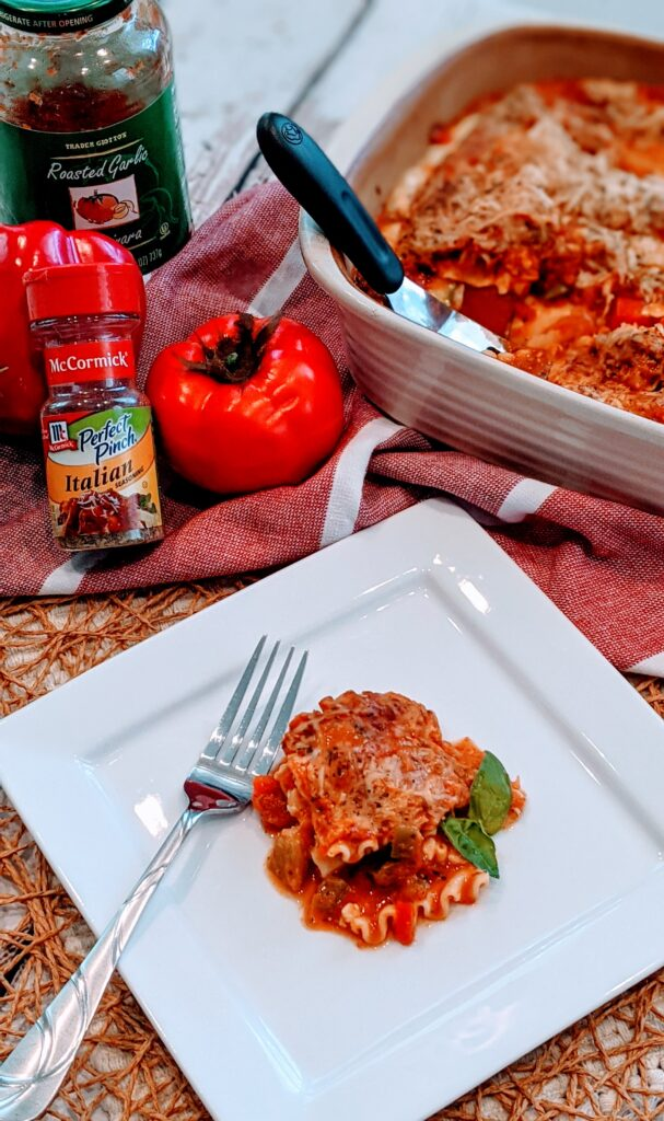 Slice of EASY CHEESY VEGETARIAN LASAGNA on individual white serving plate.