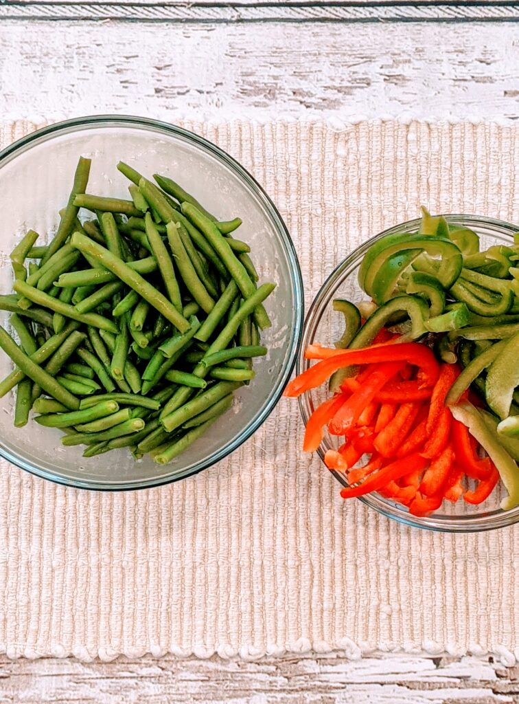 Microwaved green beans in a glass bowl and sliced peppers in a glass bowl.