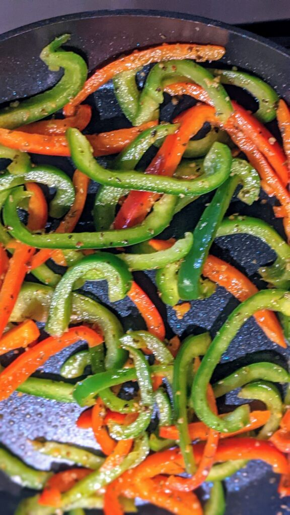 Sliced bell peppers with seasoning sautéing in a skillet.