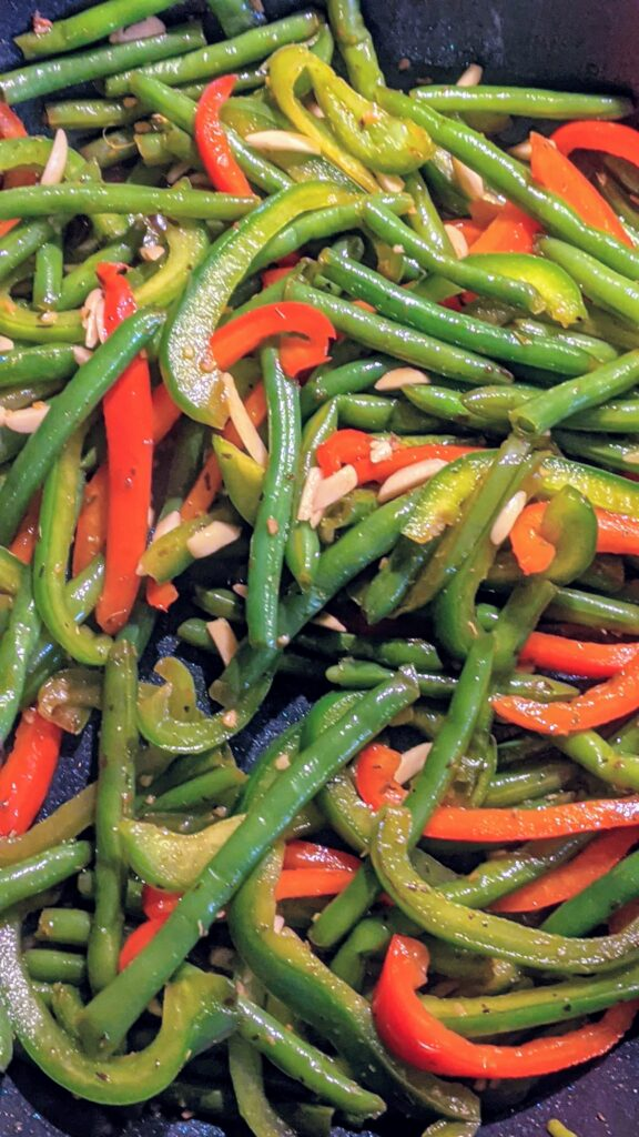 Sliced bell peppers, green beans and slivered almonds with seasoning sautéing in a skillet.