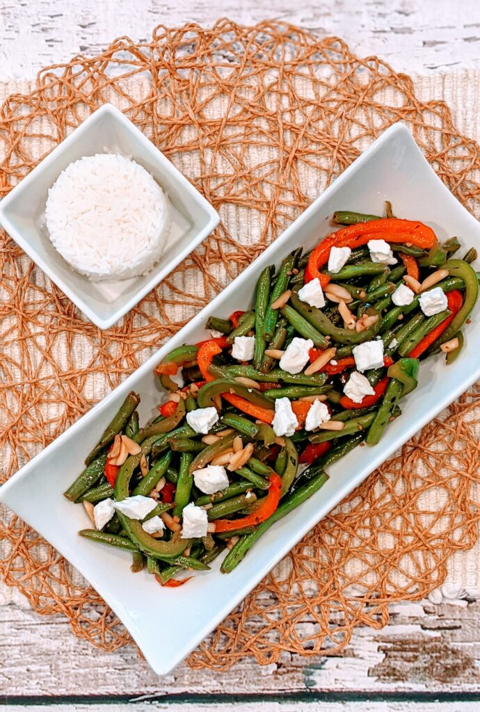 Simple Sauté Green Beans & Peppers topped with crumbled feta cheese with a side of rice.