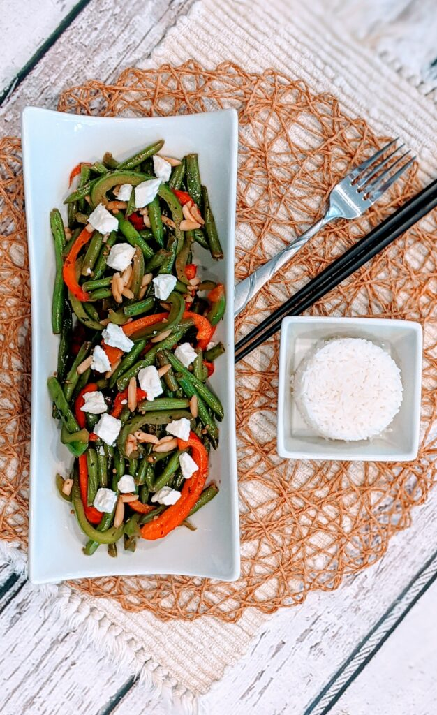 Simple Sauté Green Beans & Peppers in white serving dish ready to eat.  Side of rice along with fork and chopsticks.