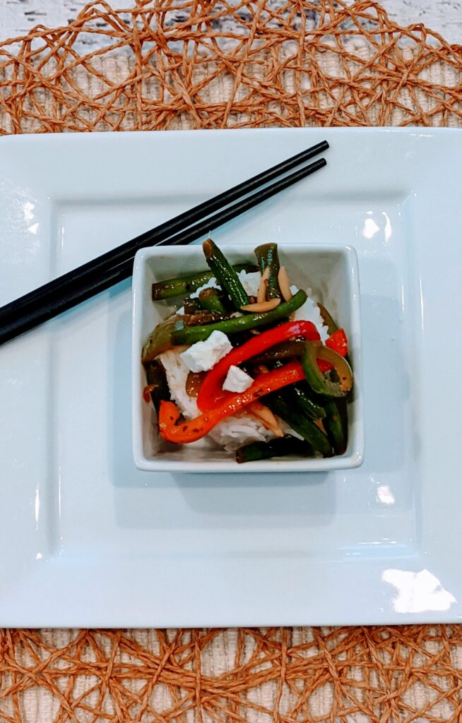 Green Beans & Peppers on top of rice in a square serving bowl on top of a square plate with chop sticks alongside.