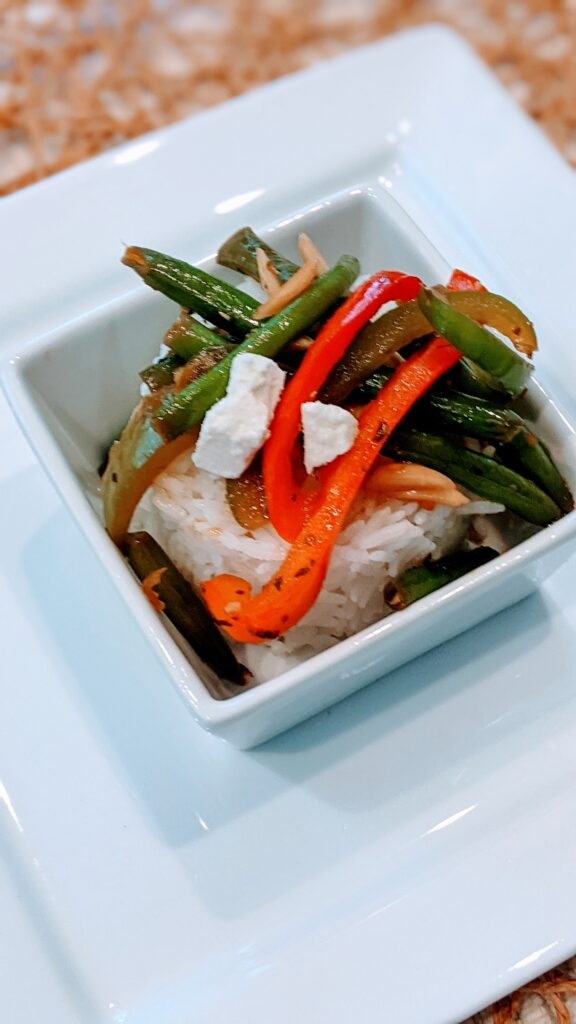 Green Beans & Peppers on top of rice in a square serving bowl.